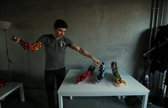 David Aguilar points at his prosthetic arms built with Lego pieces during an interview with Reuters in Sant Cugat del Valles