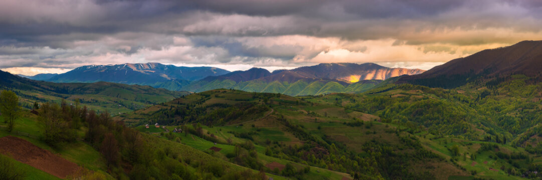 panorama of a wonderful countryside in mountains. rural fields on rolling hills. village in the distant valley. beautiful landscape in spring at sunset