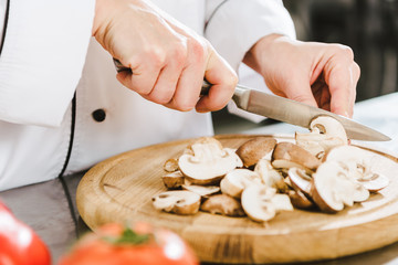 partial view of female chef cutting mushrooms in restaurant kitchen