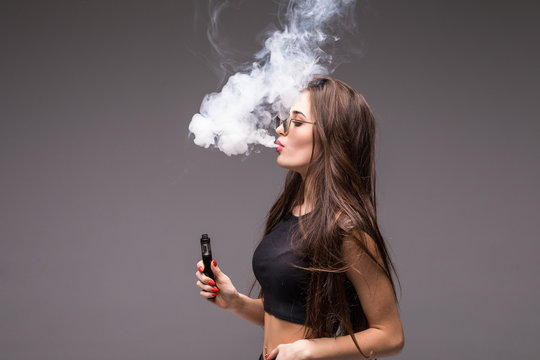 Young beauty woman wearing in sunglasses smoking vape on gray background