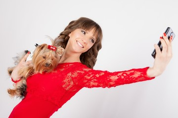 young beautiful woman with a yorkshire terrier on her hands in the photo studio makes a selfie on the phone