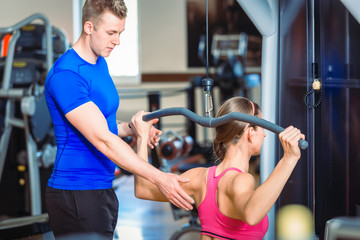 Handsome personal trainer guiding a beautiful woman at a modern fitness club