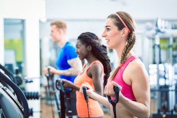 Side view of a fit happy woman cycling during cardio workout routine at the gym
