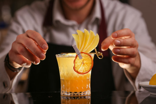 Fresh alcohol Penicillin cocktail with orange slice and ice cubes. Barmen making alcohol cocktail