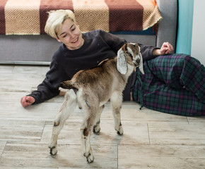 goat is standing on the floor near woman