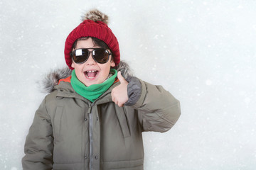 happy child with sunglasses and winter hat