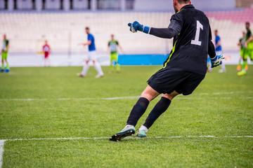 Football goalkeeper kicking the ball during football match