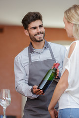 smiling worker talking to customer in wine shop