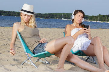 two women sit in the chairs relaxing by the sea