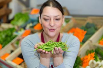 woman choosing green beans in farm food store