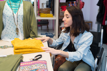 young disabled woman browsing in clothing store