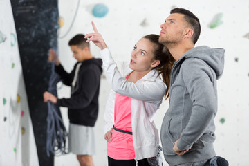 man listens to instructions on climbing by coach