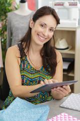 female tailor holding tablet smiling