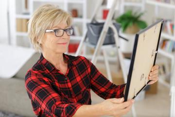 senior woman looking at frame at home