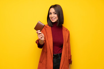 Young woman with coat holding a wallet