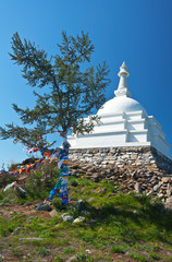 Baikal Lake. Ogoy Island in summer sunny day. White Buddhist Stupa of Enlightenment on a hill against a blue sky