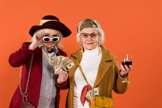 senior woman touching sunglasses while holding money near friend with glass of wine in hand isolated on orange