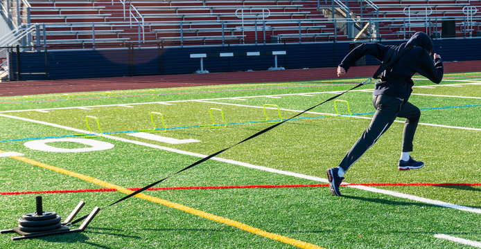 Athlete pulling sled with weights on turf field in cold weather