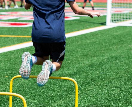 Kid jumping over yellow mini hurdle at camp