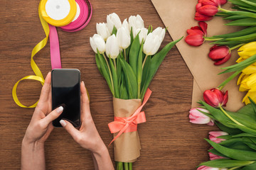 cropped view of on florist using smartphone near spring bouquet with tulips on wooden background