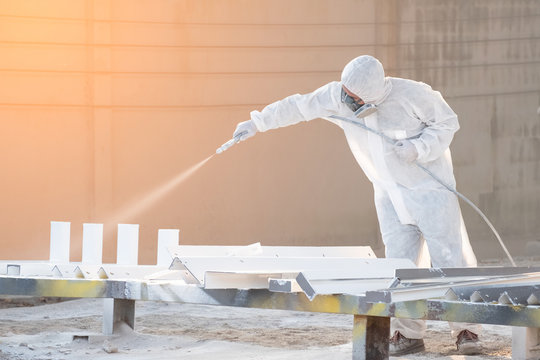 worker painting a mechanical part with airless spray