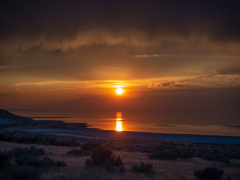 Sunset on the Antelope Island on the great Salt Lake outside the City, colorful orange dusk above a road with buffalos panorama background