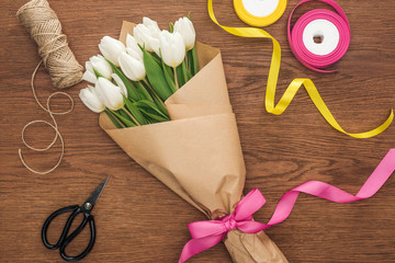 top view of spring tulip bouquet with ribbons and craft paper on wooden background