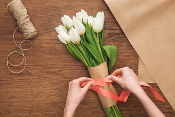 cropped view of on florist making bouquet of white spring tulips and ribbon on wooden background