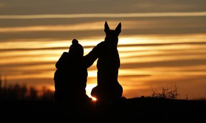 Boy and dog breed Belgian Shepherd Malinois on sunset background