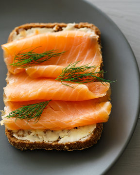 Rye sourdough toasts with butter, smoked salmon and dill. Grey ceramic plate, high resolution