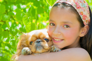Little girl holding her puppy - Stock image
