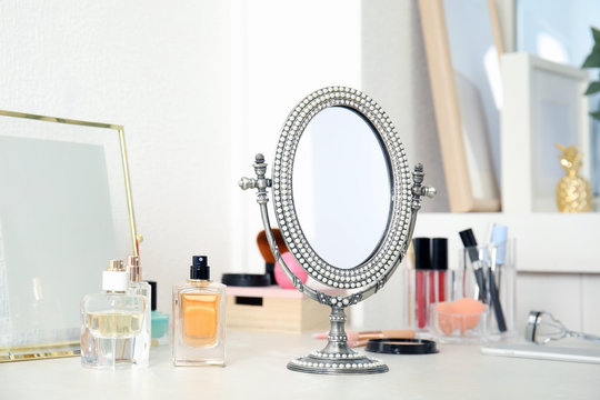 Mirror in antique frame and different cosmetics on dressing table. Beauty blogger