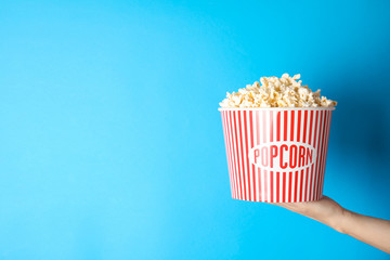 Woman holding popcorn bucket on color background, closeup with space for text. Cinema snack
