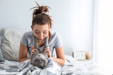 Young woman with cute cat resting on bed at home