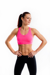 Attractive young woman in sportswear posing on white background. Healthy female model with muscular body in studio.