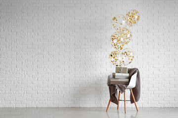 Chair with gifts and balloons near white brick wall