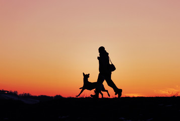 Silhouettes of man and dog on sunset background