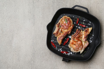 Grill pan with tasty cooked meat and spices on grey background