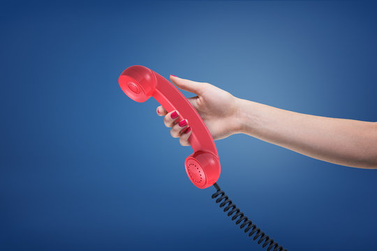 A female hand with painted nails holds a red retro phone receiver with a black cord.