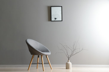 Stylish chair with vase near grey wall in room