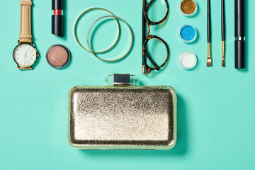 Top view of watch, lipstick, bracelets, glasses, eye shadow, blush, clutch, cosmetic brushes and mascara
