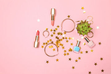 Set of makeup cosmetics with golden earrings on color background