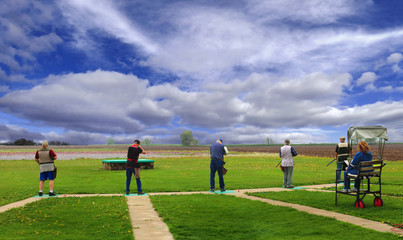 trap shooters under dramatic sky