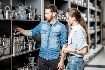 Couple choosing pans for cooking in the shop