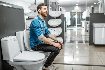 Man choosing lavatory pan sitting on it in the building shop with sanitary ceramics