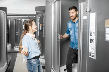 Young couple choosing a new shower cabin in the building shop with sanitary furnitures
