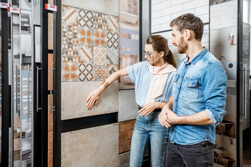 Obraz Beautiful young couple choosing ceramic tiles for their house repairment in the building shop - fototapety do salonu