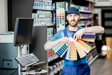 Portrait of a handsome workman with color swatches near the equipment for coloring in the building shop