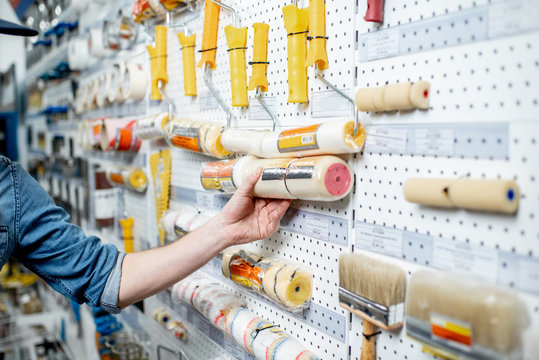 Workman choosing tools for painting in the building shop, close-up view