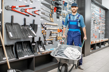 Portrait of a handsome worker in uniform standing with pushcart near the showcase with garden equipment in the shop